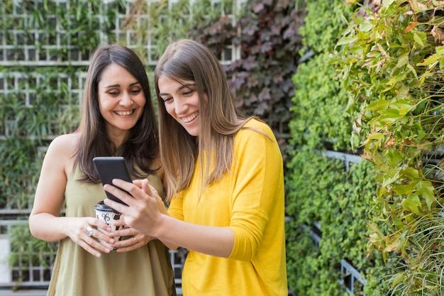 Duas mulheres lindas tomando selfie com telefone móvel. fundo verde um está segurando uma xícara de café. eles estão rindo e procurando informações no celular. estilo de vida e amizade ao ar livre Foto Premium