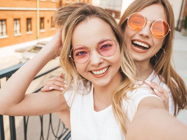 Duas mulheres loiras hipster sorridente jovens em roupas de camiseta branca de verão. meninas tirando fotos de auto-retrato de selfie no smartphone. Foto gratuita