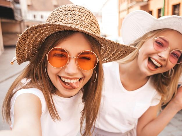 Duas mulheres loiras hipster sorridente jovens em t-shirt branca de verão. meninas tirando fotos de auto-retrato de selfie em smartphone. modelos posando na rua fundo. feminino mostra a língua e as emoções positivas Foto gratuita
