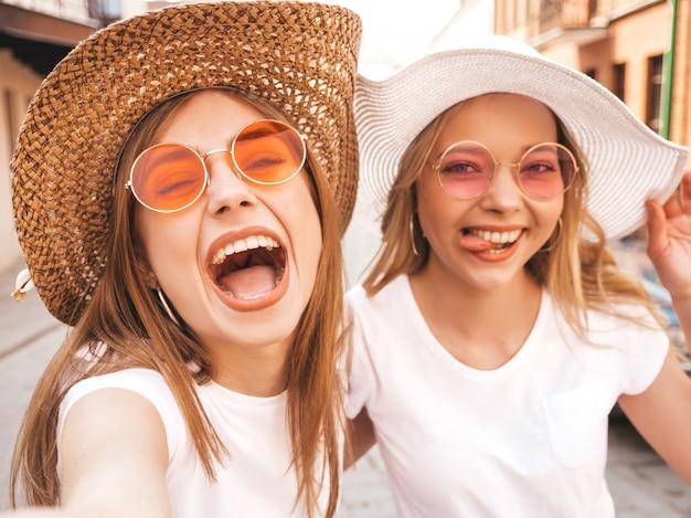 Duas mulheres loiras hipster sorridente jovens em t-shirt branca de verão. meninas tirando fotos de auto-retrato de selfie no smartphone. modelos posando na rua fundo. feminino mostra emoções positivas Foto gratuita