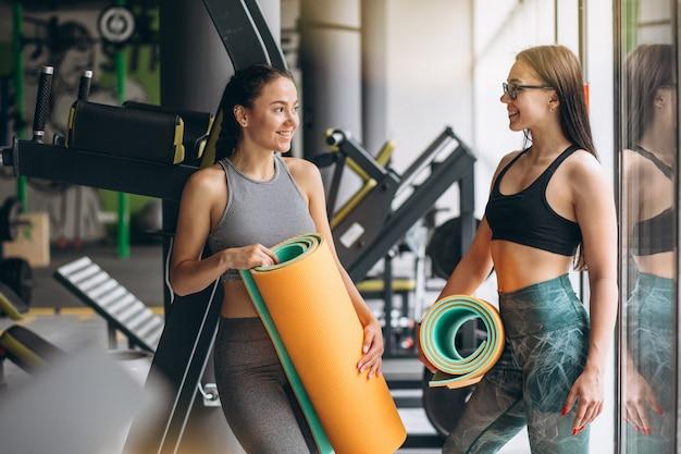 Duas mulheres na academia segurando o tapete de ioga Foto gratuita