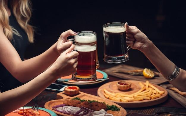 Duas mulheres na mesa de jantar com copos de cerveja. Foto gratuita