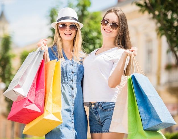 Duas mulheres novas bonitas que apreciam a compra. Foto Premium
