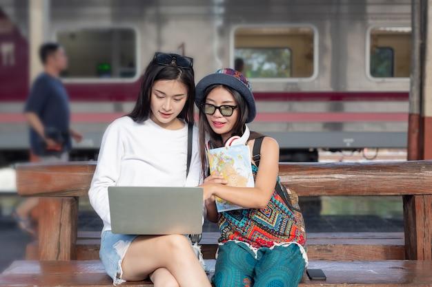 Duas mulheres são felizes jogando um notebook enquanto viaja na estação de trem. conceito de turismo Foto gratuita