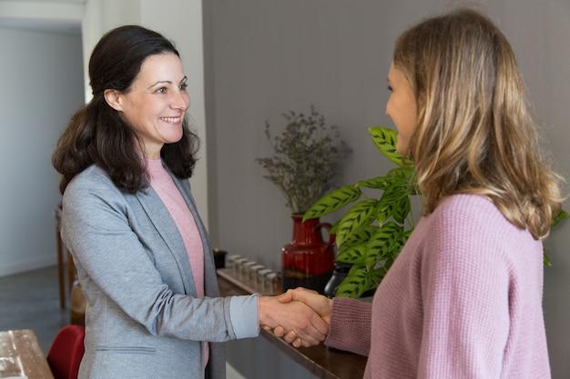 Duas mulheres sorridentes de pé e apertando as mãos Foto gratuita