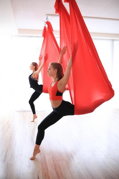 Duas mulheres treinando ginástica no centro de yoga Foto gratuita