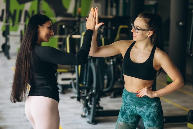 Duas mulheres treinando juntos na academia Foto gratuita