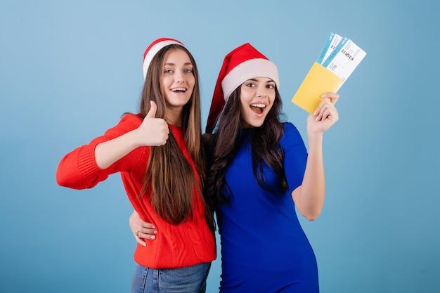 Duas mulheres vestindo chapéus de papai noel com bilhetes de avião e passaporte isolado sobre o azul Foto Premium