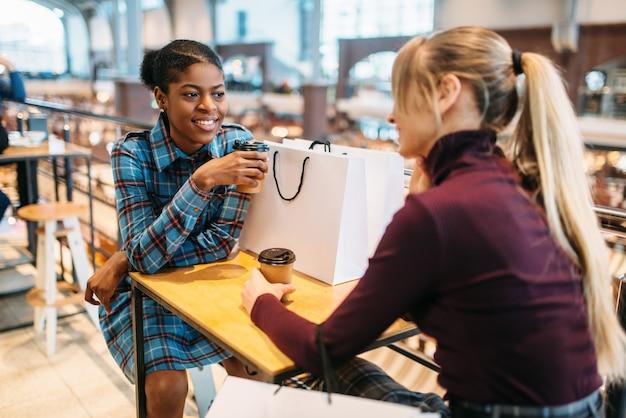 Duas namoradas na praça de alimentação depois de fazer compras Foto Premium