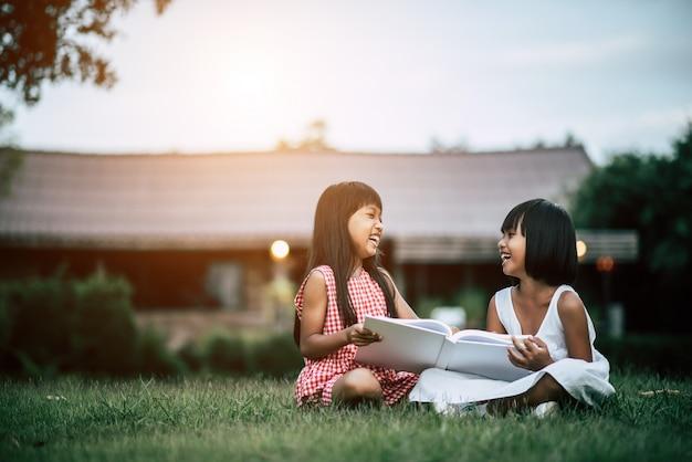 Duas namoradinhas no parque na grama lendo um livro e aprender Foto gratuita