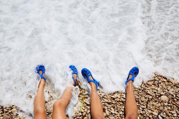 Duas pernas de garotinha em uma costa de espuma de praia Foto Premium