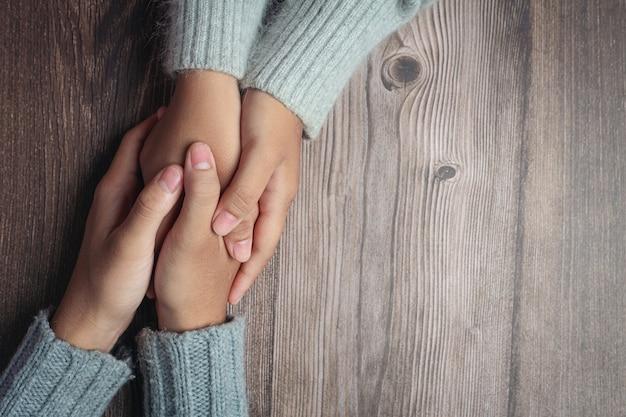 Duas pessoas de mãos dadas com amor e carinho na mesa de madeira Foto gratuita