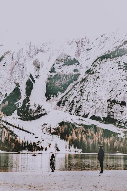 Duas pessoas em pé na costa, com vista para o corpo de água e a montanha coberta de neve Foto gratuita