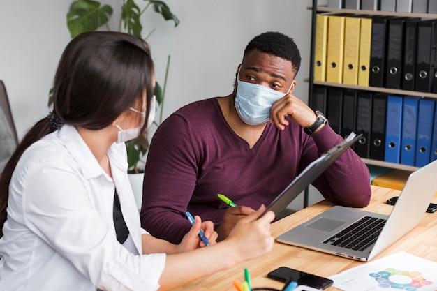 Duas pessoas no escritório trabalhando juntas durante a pandemia com máscaras médicas Foto gratuita