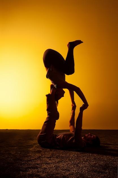 Duas pessoas praticando ioga na luz do sol Foto gratuita