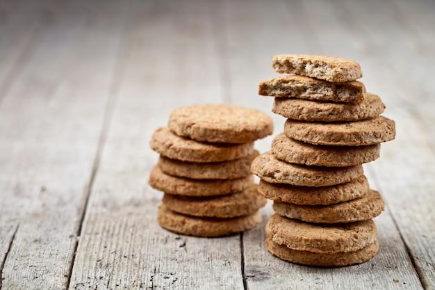 Duas pilhas de biscoitos de aveia frescos na mesa de madeira rústica Foto Premium