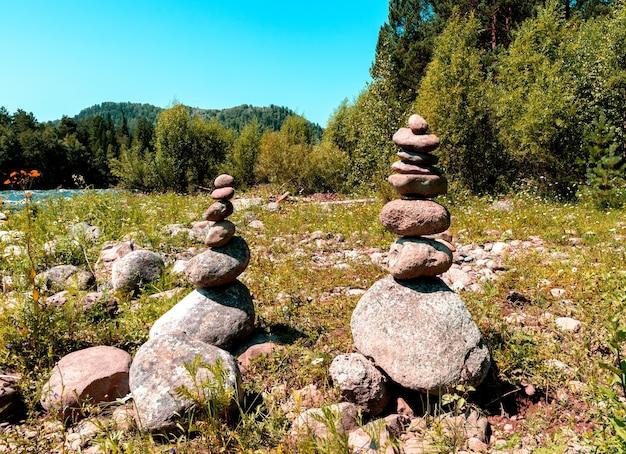 Duas pirâmides feitas de pedras nas margens de um rio de montanha. lugar de poder de altai Foto Premium