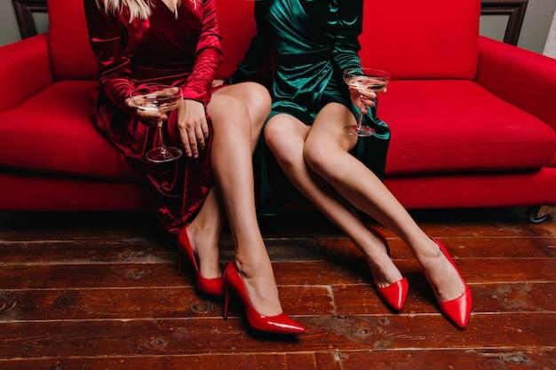 Duas senhoras com sapatos vermelhos, sentadas no sofá. glamourosas amigas bebendo vinho enquanto posam no sofá. Foto gratuita