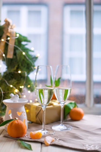 Duas taças de champanhe, frutas em cima da mesa perto da janela Foto Premium