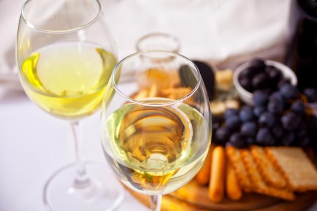 Duas taças de vinho branco e prato com diversos queijos e frutas Foto Premium