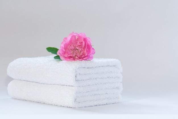 Duas toalhas de terry dobradas ordenadamente brancas com uma flor de rosa Foto Premium