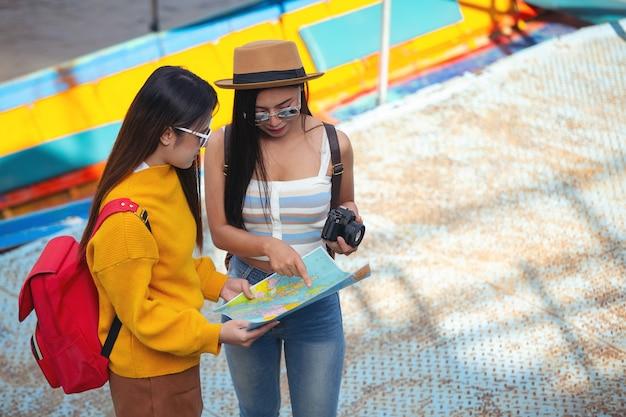 Duas turistas do sexo feminino segurar um mapa para encontrar lugares. Foto gratuita