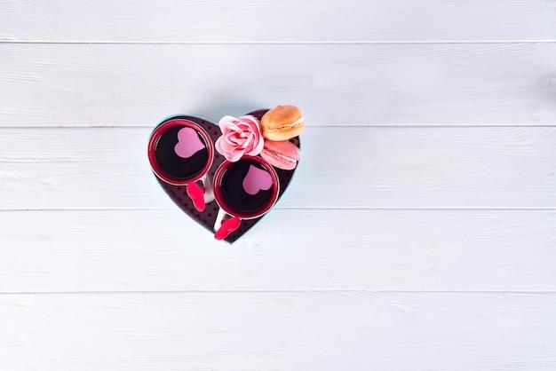 Duas xícaras de café, bolinhos de amêndoa, flores em um formulário da caixa de um coração em um fundo branco. Foto Premium