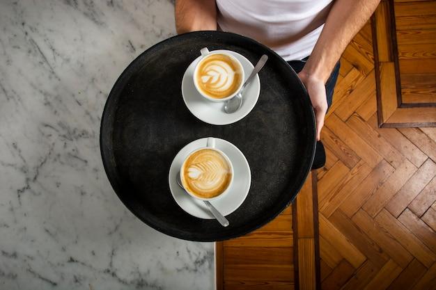 Duas xícaras de café com latte art na bandeja Foto gratuita