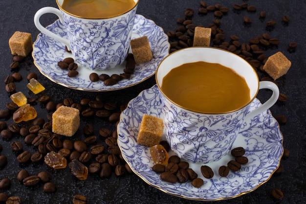Duas xícaras de café e grãos de café sobre fundo preto Foto Premium