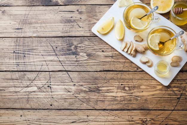 Duas xícaras de chá de ervas naturais gengibre limão e mel numa superfície de madeira. Foto Premium