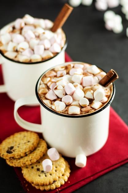 Duas xícaras de chocolate quente, cacau ou bebida quente com marshmallows e biscoitos doces no escuro Foto Premium