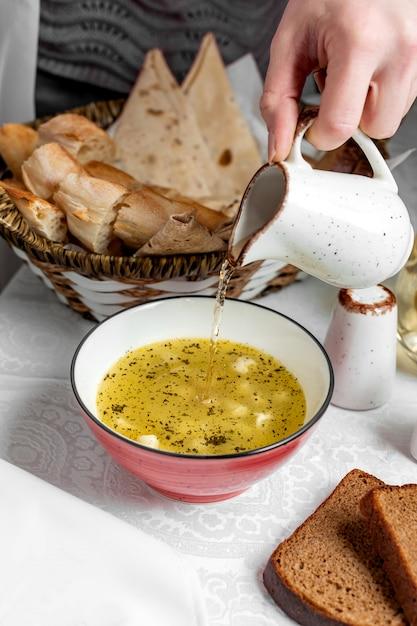 Dushbara em caldo polvilhado com hortelã seca derramada com vinagre Foto gratuita