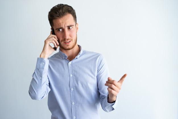 Duvidoso empresário apontando o dedo para longe Foto gratuita