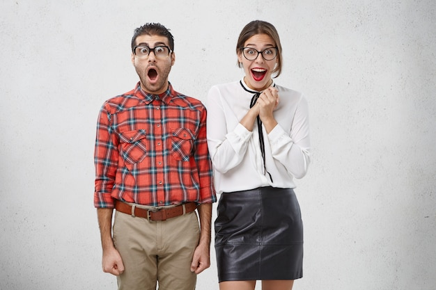 É inacreditável! homem chocado olha surpreso através dos óculos, fica de boca aberta, ouve notícias inesperadas e alegre Foto gratuita