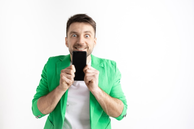 É legal. boas notícias. faça isso como eu. jovem bonito mostrando a tela do smartphone e assinando o sinal de ok isolado no fundo cinza. emoções humanas, expressão facial, conceito de publicidade. Foto gratuita
