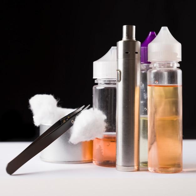 E-líquidos, algodão, pinças e cigarros eletrônicos para vaping Foto Premium