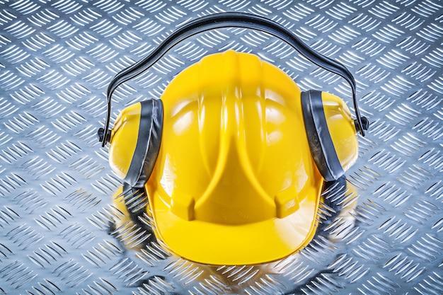 Earmuffs, capacete de construção no conceito de construção de fundo de metal sulcado Foto Premium