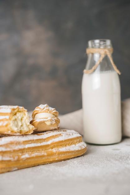 Eclair caseiro cozido fresco com garrafa de leite Foto gratuita