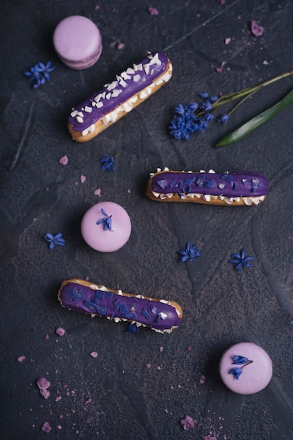 Eclair roxo mirtilo com macaroons em fundo preto texturizado Foto gratuita