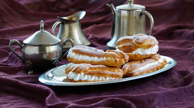 Eclairs, choux pastries cheios de chantilly, fundo violeta escuro, louça de prata Foto Premium