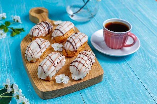 Eclairs ou profiteroles com chocolate preto e chocolate branco com creme para dentro, sobremesa francesa tradicional. vista superior. Foto gratuita