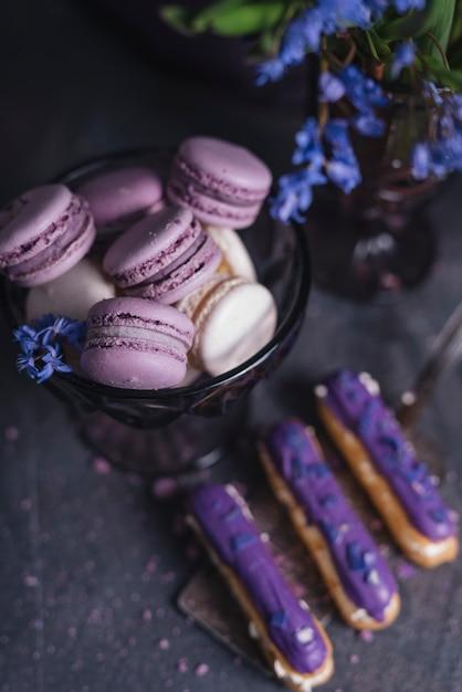 Eclairs roxos na espátula com macaroons na tigela de vidro perto do vaso Foto gratuita