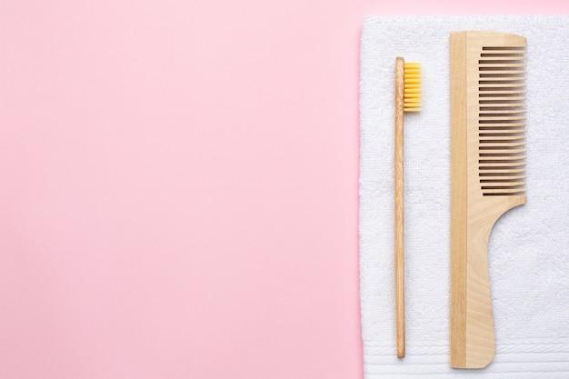 Eco escova de dentes de madeira, pente e toalha de banho branca em rosa Foto Premium