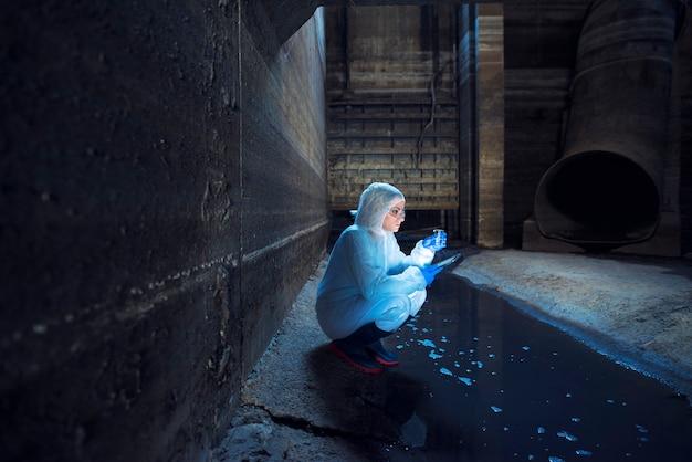 Ecologista colhendo amostra de água do sistema de esgoto e examinando a qualidade e o nível de contaminação e poluição Foto gratuita