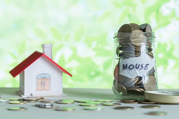 Economia de dinheiro para casa na garrafa de vidro. Foto gratuita