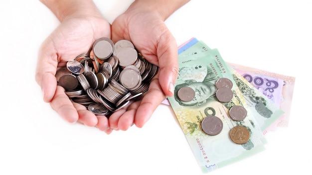 Economizando dinheiro coletando moedas e notas de dinheiro tailandesas. Foto Premium