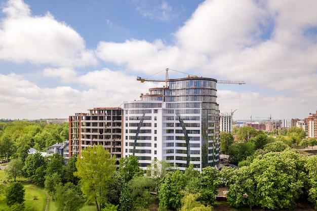 Edifício alto de apartamento ou escritório inacabado em construção entre copas de árvores verdes. Foto Premium