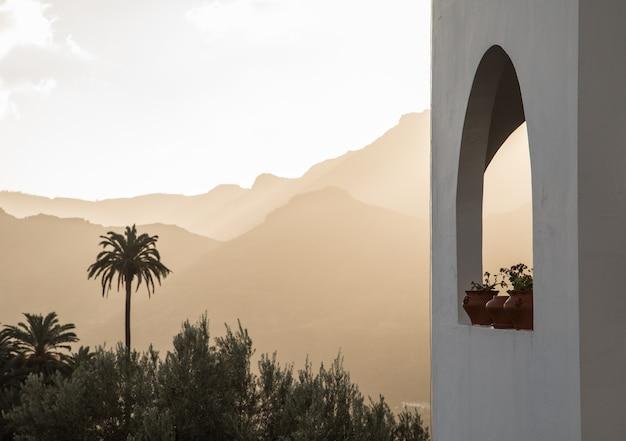 Edifício branco com janela em arco com plantas, palmeiras e montanhas Foto Premium