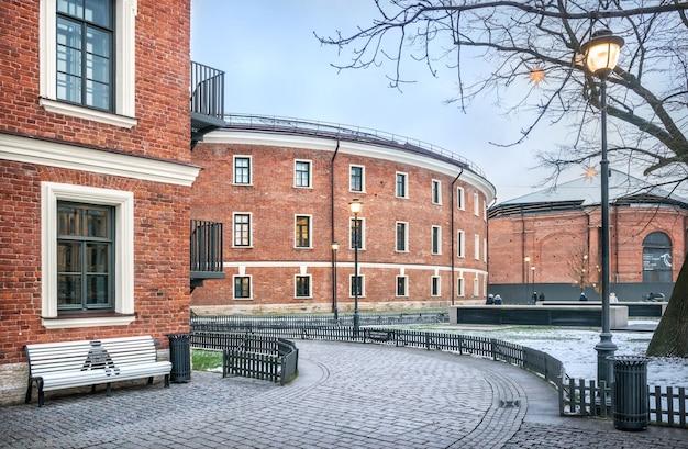 Edifício de tijolos da new holland em são petersburgo e um banco branco Foto Premium