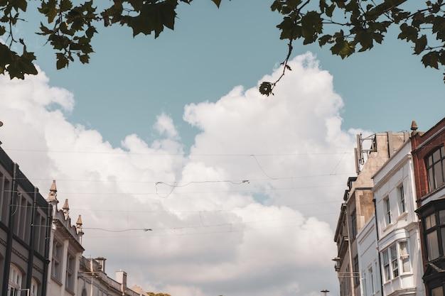 Edifícios antigos e os cabos de cabos sob as nuvens no céu Foto gratuita